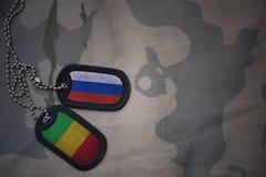 wojska puste miejsce, psia etykietka z flaga Russia i Mali na khakim tekstury tle, Obraz Stock