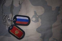 wojska puste miejsce, psia etykietka z flaga Russia i Montenegro na khakim tekstury tle, Fotografia Royalty Free