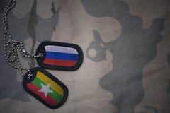 wojska puste miejsce, psia etykietka z flaga Russia i Myanmar na khakim tekstury tle, Zdjęcie Stock