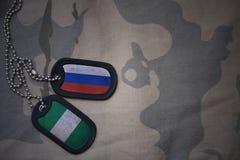 wojska puste miejsce, psia etykietka z flaga Russia i Nigeria na khakim tekstury tle, Obraz Stock