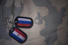 wojska puste miejsce, psia etykietka z flaga Russia i Paraguay na khakim tekstury tle, Fotografia Royalty Free