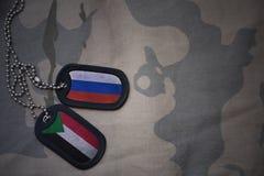 wojska puste miejsce, psia etykietka z flaga Russia i Sudan na khakim tekstury tle, Zdjęcie Royalty Free