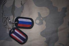 wojska puste miejsce, psia etykietka z flaga Russia i Thailand na khakim tekstury tle, Zdjęcia Royalty Free