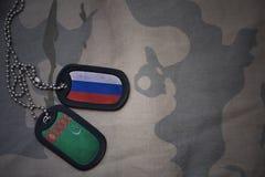 wojska puste miejsce, psia etykietka z flaga Russia i Turkmenistan na khakim tekstury tle, Fotografia Stock