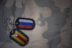 wojska puste miejsce, psia etykietka z flaga Russia i Zimbabwe na khakim tekstury tle, Obrazy Stock