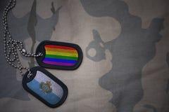 wojska puste miejsce, psia etykietka z flaga San marino i homoseksualista tęcza, zaznaczamy na khakim tekstury tle Fotografia Royalty Free