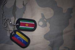 wojska puste miejsce, psia etykietka z flaga Suriname i Venezuela na khakim tekstury tle, Obraz Stock