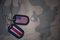 wojska puste miejsce, psia etykietka z flaga zlani stany America i costa rica na khakim tekstury tle, Obrazy Stock