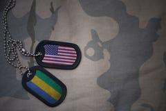 wojska puste miejsce, psia etykietka z flaga zlani stany America i Gabon na khakim tekstury tle, Fotografia Stock