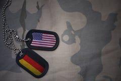 wojska puste miejsce, psia etykietka z flaga zlani stany America i Germany na khakim tekstury tle, Obraz Royalty Free