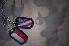 wojska puste miejsce, psia etykietka z flaga zlani stany America i Indonesia na khakim tekstury tle, zdjęcie stock
