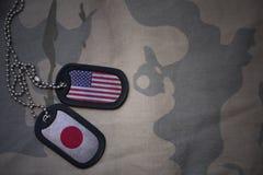 wojska puste miejsce, psia etykietka z flaga zlani stany America i Japan na khakim tekstury tle, Obraz Stock