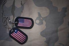 wojska puste miejsce, psia etykietka z flaga zlani stany America i Liberia na khakim tekstury tle, Fotografia Royalty Free
