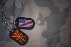 wojska puste miejsce, psia etykietka z flaga zlani stany America i Macedonia na khakim tekstury tle, Zdjęcie Stock