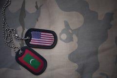 wojska puste miejsce, psia etykietka z flaga zlani stany America i Maldives na khakim tekstury tle, Zdjęcia Royalty Free