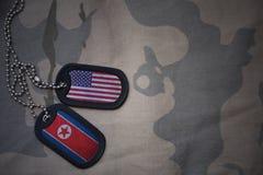 wojska puste miejsce, psia etykietka z flaga zlani stany America i północny Korea na khakim tekstury tle, Fotografia Royalty Free