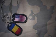wojska puste miejsce, psia etykietka z flaga zlani stany America i Romania na khakim tekstury tle, zdjęcia stock