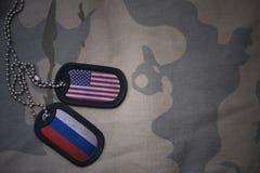 wojska puste miejsce, psia etykietka z flaga zlani stany America i Russia na khakim tekstury tle, Fotografia Royalty Free