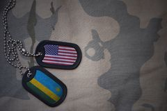 wojska puste miejsce, psia etykietka z flaga zlani stany America i Rwanda na khakim tekstury tle, Zdjęcia Royalty Free