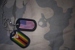 wojska puste miejsce, psia etykietka z flaga zlani stany America i Zimbabwe na khakim tekstury tle, Obraz Royalty Free