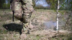 Wojskowego żołnierz lub wojownik chodzimy w butach, dotykamy linową rozciągliwość od oklepiec kopalni i wybuchamy dymi zdjęcie wideo
