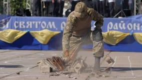 Wojskowy w żołnierza ` s munduru roztrzaskaniach podpala z jego rękami przeciw tłu scena w na wolnym powietrzu zdjęcie wideo