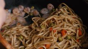 Wok με τις γαρίδες που αναμιγνύονται σε ένα τηγάνι φιλμ μικρού μήκους