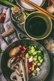Wok avec les légumes et les épices coupés sur le fond de table de cuisine avec les baguettes, la sauce de soja et l'huile de sésa photos stock