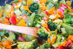 Wok closeup, a healthy vegetable dish with wooden spoon stock images