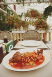 Wok cooked carp on restaurant table, toned. Carp cooked in wok on restaurant table, summer terrace, toned image Stock Image