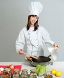 Wok cooking lesson. Young chef in a neutral background giving a cooking lesson Royalty Free Stock Photos