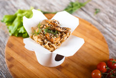 Wok noodles with chicken in paper packaging. Delicious wok noodles box container with udon and chicken on wooden table. Chinese and asian takeaway fast food Stock Image