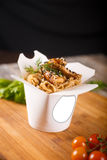 Wok noodles with chicken in paper packaging. Delicious wok noodles box container with udon and chicken on wooden table. Chinese and asian takeaway fast food Royalty Free Stock Photo