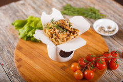 Wok noodles with chicken in paper packaging. Delicious wok noodles box container with udon and chicken on wooden table. Chinese and asian takeaway fast food Stock Images