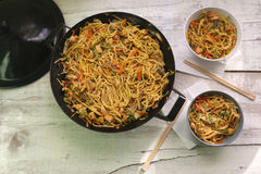 Wok. Noodles with chicken and various vegetables, prepared and served in wok. Two smaller bowls with chopsticks on the side. Served on white rustic table. Top Royalty Free Stock Image
