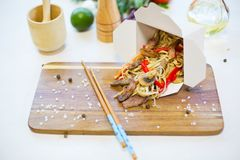Wok. Noodles with vegetables and beef in take-out box on wooden table.  Royalty Free Stock Photography