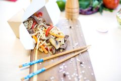 Wok. Noodles with vegetables and beef in take-out box on wooden table.  Stock Photography