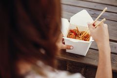Wok with noodles and vegetables in carton box to go and bamboo chopsticks. Traditional Asian cuisine. Asian Street food festival. Girl eating thai noodles in royalty free stock photo
