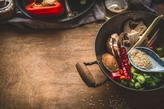 Wok pot with vegetarian asian cuisine ingredients for stir fry with chopped vegetables, spices, sesame seeds and lemongrass on rus royalty free stock photo