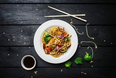 Wok. Udon stir fry noodles with chicken and vegetables in a white plate on black wooden background. With chopsticks and. Sauce. Top view royalty free stock photo