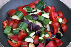 Wok with vegetables. Mixed vegetables in Wok, cut ready for cooking with olive oil Stock Image