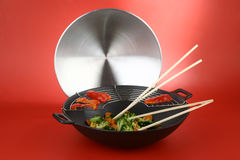 Wok with vegetables and lid. On a red background Royalty Free Stock Photo