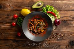 Wok vegetables with spices in a black plate stock image