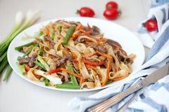 woka Nudlar med kött och grönsaker i kines arkivbild