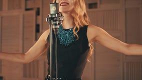 Wokalista w rozjarzonej sukni wykonuje na scenie przy mikrofonem Podwyżek ręki taniec zdjęcie wideo