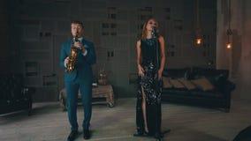 Wokalista w rozjarzonej sukni wykonuje na scenie z saksofonisty Retro stylem jazzes zbiory