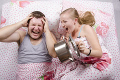 She woke and frightened the boy in the bed, slamming the lid on the pan. A couple lying in bed. Girl brutally awakened a sleeping guy, slamming the lid on the Royalty Free Stock Image