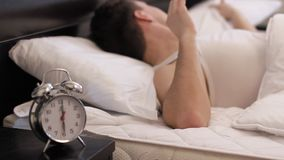 Woken up by alarm clock stock footage