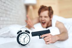 Woken up evil man is aims gun at alarm clock royalty free stock photography