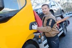 Woker эвакуатора портрета с отбуксированным автомобилем стоковые изображения rf